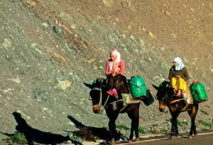 Girls on donkeys carrying jugs of water