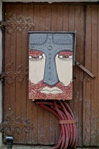 Old meets new: street art electrical box on a medieval door