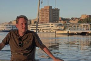 Aaron with modern Aswan in the background