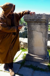 Our guide reading Latin at ancient Roman ruin Volubilis